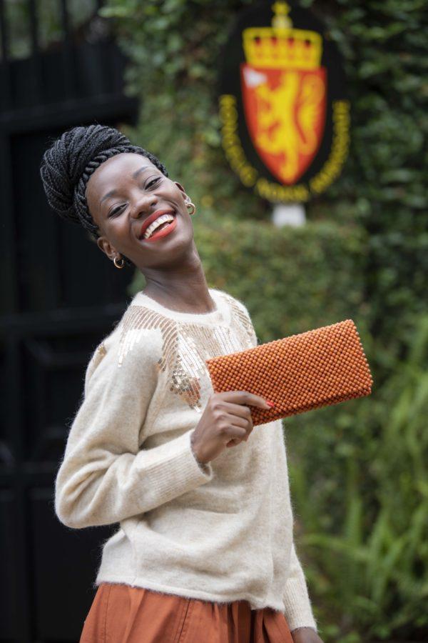 Modell med oransje clutch fra 4Africa